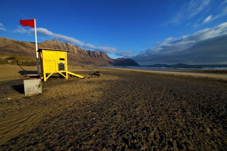 lifeguard chair red flag in spain  lanzarote  rock stone sky cloud beach  water  musk pond  coastline and summer   photo