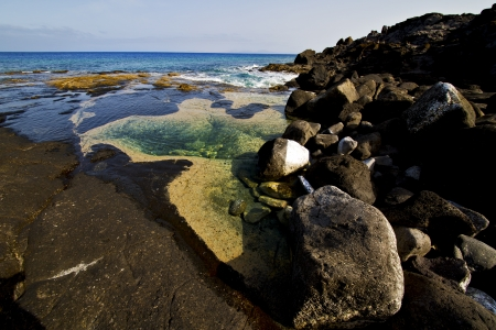 landscape rock stone sky cloud beach   water  in lanzarote spain isle   photo