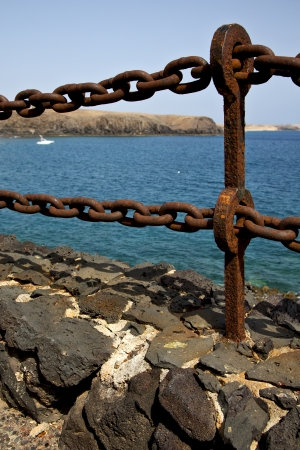 stell: rusty chain  water  boat yacht coastline and summer in lanzarote spain  Stock Photo