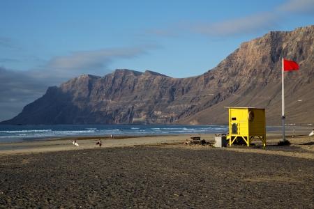 Pr�sidence de ma�tre nageur drapeau rouge en Espagne Lanzarote roche, pierre, ciel plage c�te �tang musc nuage d'eau et d'�t� Banque d'images