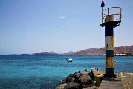 lighthouse and pier boat in the blue sky   arrecife teguise lanzarote spain  photo