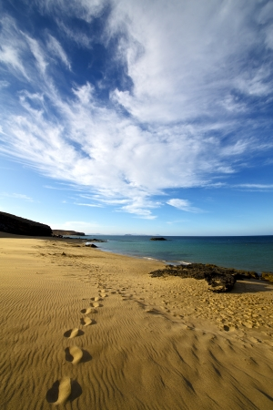 footstep in lanzarote   spain  rock stone sky cloud beach  water  musk pond  coastline and summer   photo