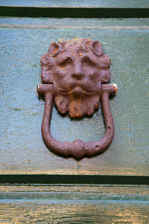 abstract  rusty brass brown knocker in a   closed wood door olgiate olona varese italy photo
