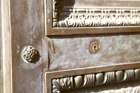 brebbia abstract   rusty brass brown knocker in a  door curch  closed wood italy  lombardy photo