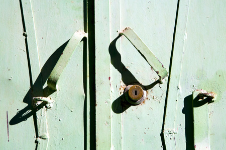 metal   green    morocco in    africa the old wood  facade home and rusty safe padlock photo