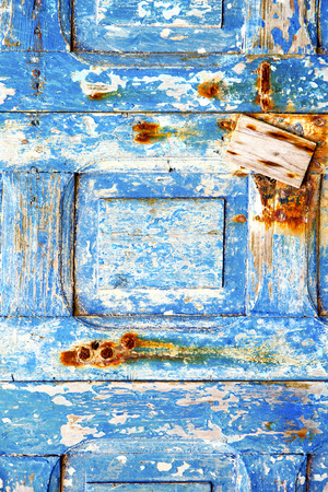stripped: blue stripped paint in the wood door and rusty nail