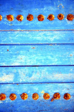 rusty nail: Despojado de pintura en la puerta de madera azul y clavo oxidado Foto de archivo