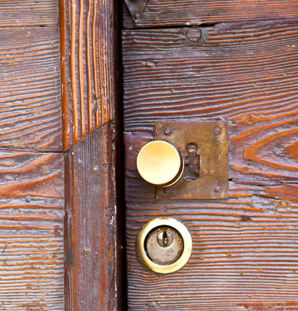 brass brown knocker and wood  door vinago  varese italy photo