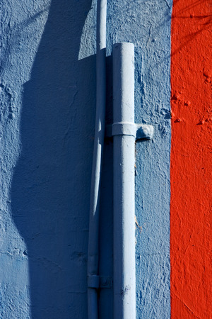 la boca: blue colored pipe and red wall in la boca  buenos aires  argentina
