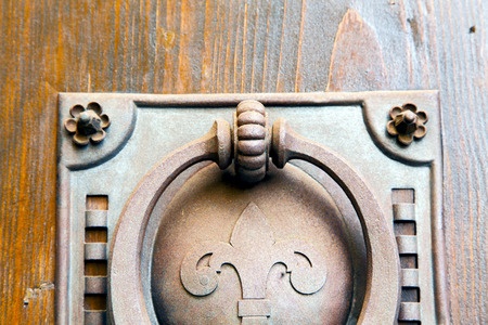 curch: castellanza blur lombardy   abstract   rusty brass brown knocker in a  door curch  closed wood italy   cross