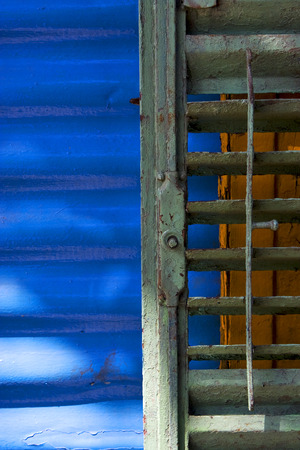 la boca: green iron venetian blind and a blue metal wall in la boca buenos aires argentina Stock Photo
