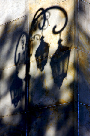 shadow of a street lamp  and a yellow orange marble  wall  in la boca buenos aires argentina photo