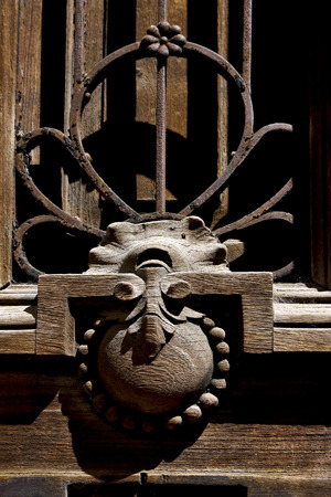 metal tips: brass brown knocker in a closed brown wood  door buenos aires argentina