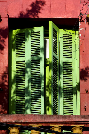 la boca: old  yellow little terrace green venetian blind and roof  in the centre of buenos aires la boca argentina