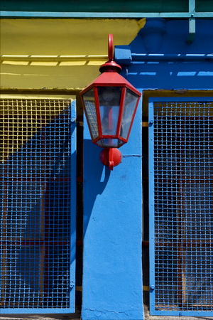 la boca: a red street lamp  and a yellow blue wall  in la boca buenos aires argentina Stock Photo