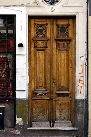 grate: a brown wood old door and a grate in the centre of buenos aires argentina