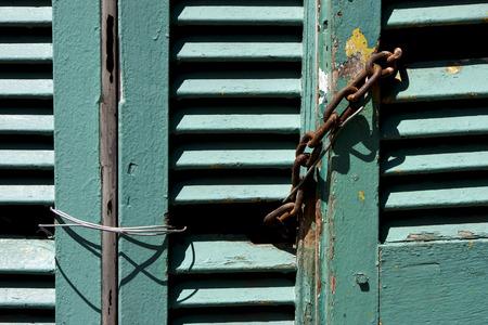 la boca: light green wood venetian blind and a rusty chain in la boca buenos aires argentina Stock Photo