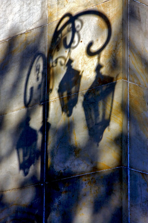 la boca: shadow of a street lamp  and a yellow orange marble  wall  in la boca buenos aires argentina