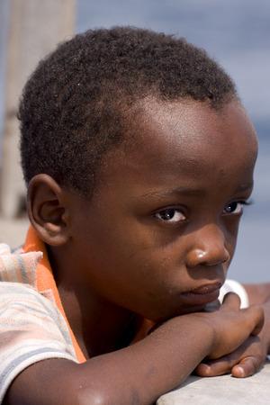 bambino: a sad little boy in a boat in zanzibar