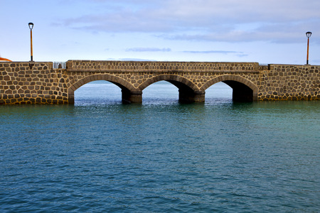 atlantic ocean lanzarote  bridge and street lamp in the blue sky   arrecife teguise spain photo