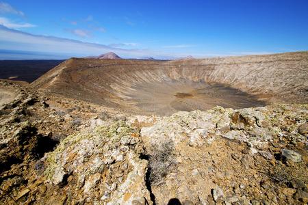 timanfaya: in los volcanes volcanic timanfaya  rock stone sky  hill and summer  lanzarote spain plant flower bush Stock Photo