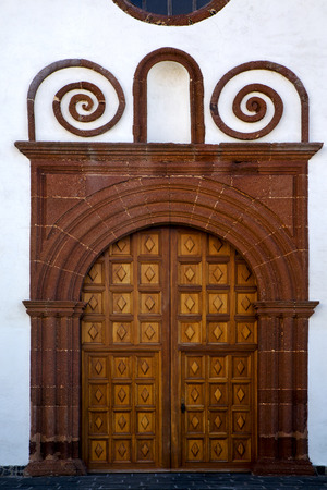canarias: lanzarote  spain canarias brass brown knocker in a   closed wood  church door and white wall abstract Stock Photo