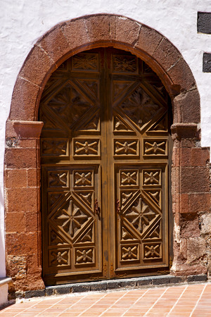 canarias: lanzarote  spain canarias brass brown knocker in a   closed wood  church door and white wall abstract Editorial