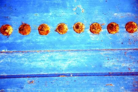 rusty nail: pintura despojada en la puerta de madera azul y clavo oxidado Foto de archivo