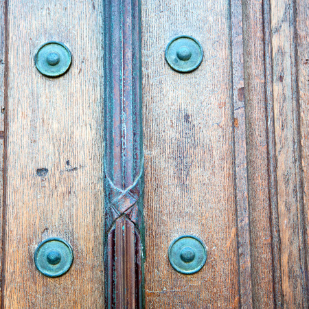 rusty nail: in london antique brown door  rusty  brass nail and light Stock Photo