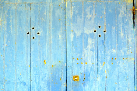 rusty nail: stripped paint in the blue wood door and rusty nail Stock Photo