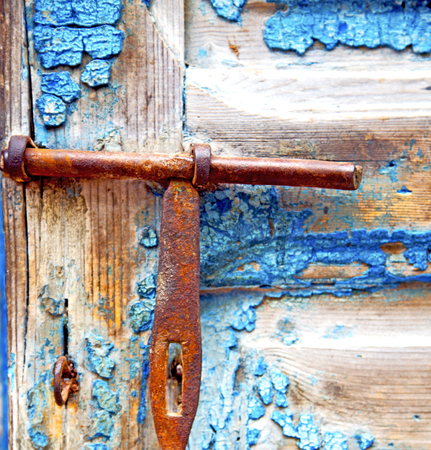 rusty nail: metal nail dirty     stripped paint in the brown   red wood door and rusty  knocker