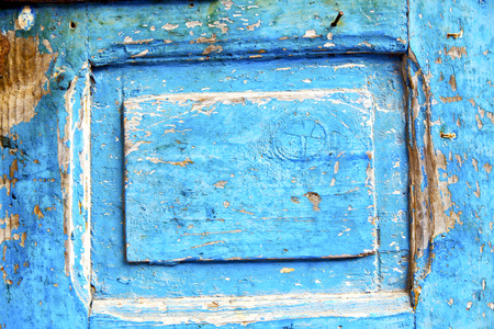 rusty nail: stripped paint in the blue wood door and rusty nail Editorial