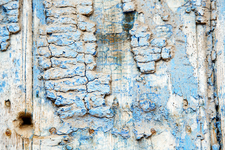rusty: stripped paint in the blue  wood door    and rusty      nail