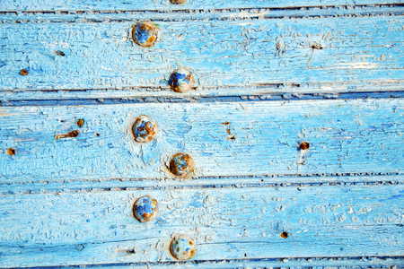 stripped: stripped paint in the blue wood door and rusty  nail Stock Photo