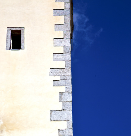 sunny day: cross sumirago lombardy italy  varese abstract   wall of a curch broke brike pattern sunny day  and sky