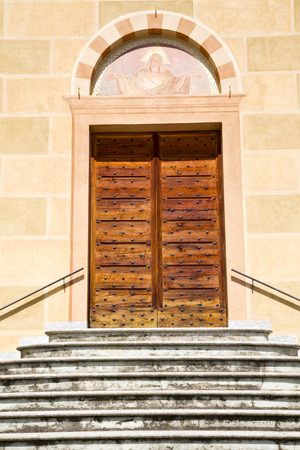 sunny day: sunny daY italy church tradate  varese  the old door entrance and mosaic