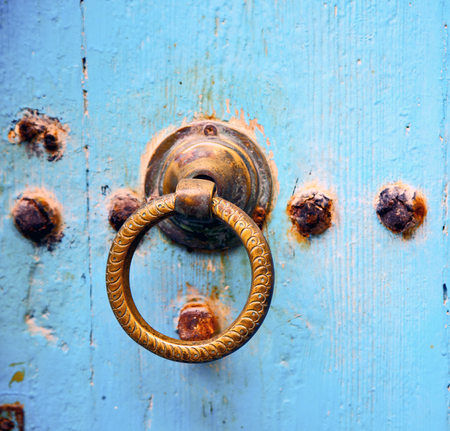 knocker: metal nail dirty stripped paint in the brown   red wood door and rusty  knocker