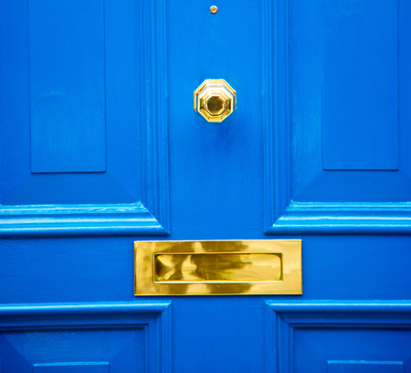 door handle: blue handle  in london antique  door  rusty  brass nail and light