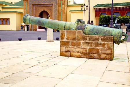 bronze cannon in africa morocco  green  and the old pavement