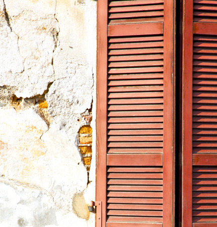 venetian blind: red window  varano borghi italy   abstract  sunny day    wood venetian blind in the concrete  brick