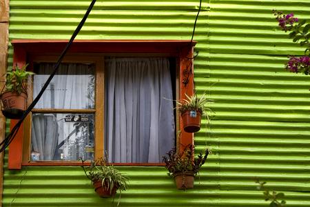 la boca: orange wood window and a green metal wall in la boca buenos aires argentina Stock Photo