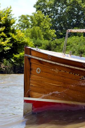 tigre: red prow boat water and coastline in rio de la plata el tigre buenos aires argentina