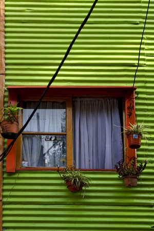 la boca: orange wood window and a green metal wall in la boca buenos aires argentina Stock Photo