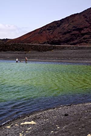 dog rock: street people dog stone  atlantic ocean sky  water lanzarote in el golfo  spain musk pond rock  coastline and summer