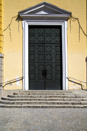 brass brown knocker and wood  door in a church crenna gallarate varese italy