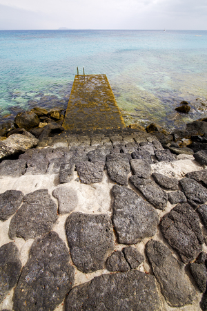 stell: pier rusty chain  water  boat yacht coastline and summer in lanzarote spain Stock Photo