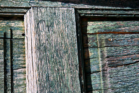 distort: a green piece of wood  brown knocker and wood  door cairate varese italy