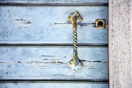 cross lombardy   arsago seprio abstract   rusty brass brown knocker in a  door curch  closed wood italy Stock Photo