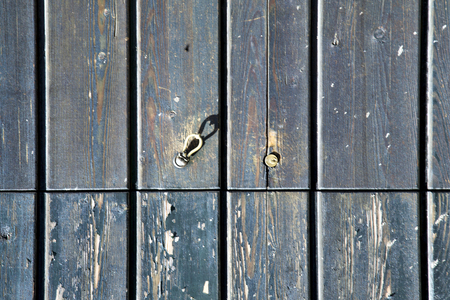 curch: sumirago varese   abstract   rusty brass brown knocker in a  door curch  closed wood lombardy italy