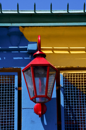 la boca: red street lamp  and a colorated  wall in la boca buenos aires argentina